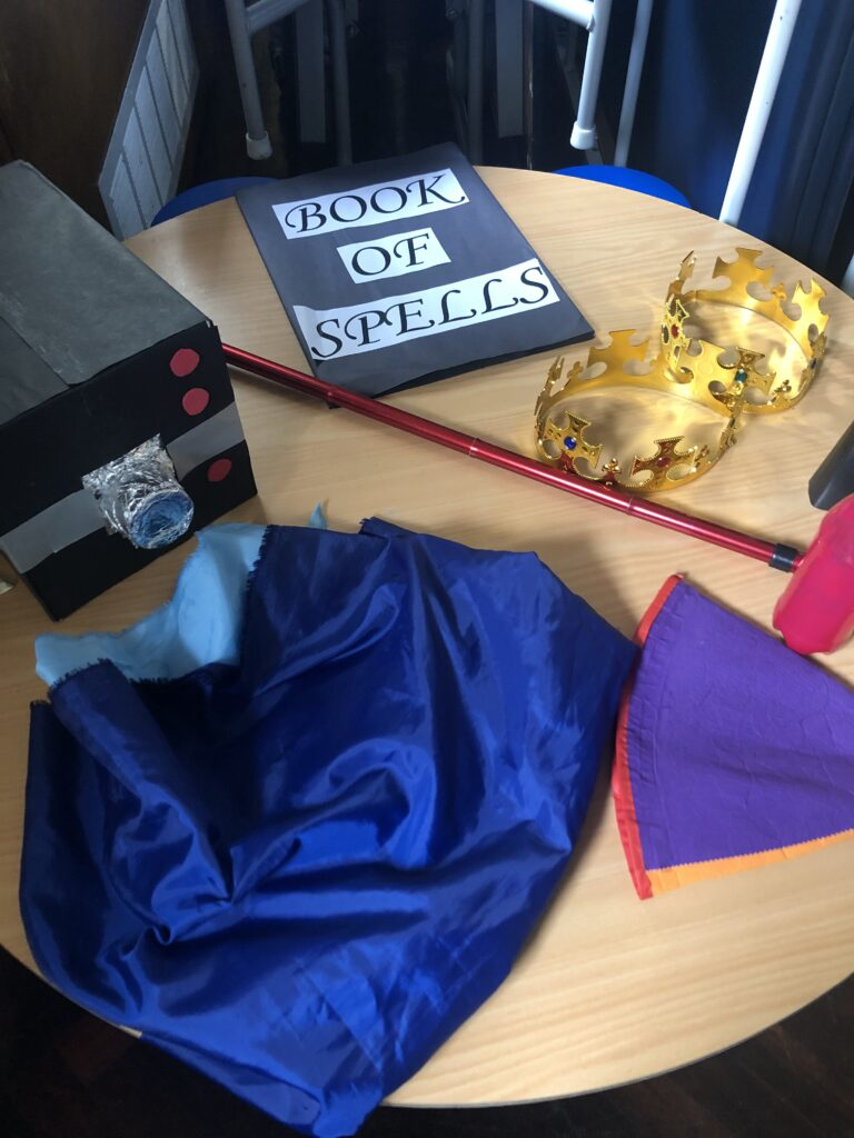 Prop table for The Tempest at St Botolph's, Peterborough.Cardboard box camera, Book Of Spells, 2 crowns, 1 walking stick, Trinculo hat and a blue material representing a wave!